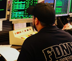 An FDNY dispatcher takes calls in the dispatch center. (Photo/NYC.gov)
