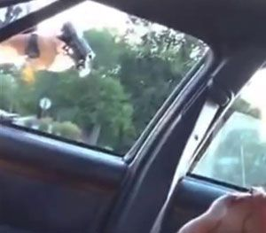 This still image taken from video by Diamond Reynolds shows a police officer pointing a gun at her boyfriend, Philando Castile, during a traffic stop on Wednesday, July 6, 2016 in Falcon Heights, Minn. (AP Image)
