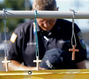 Millville, N.J. police chaplain Robert Ossler prays Monday, July 18, 2016, at a makeshift memorial at the fatal shooting scene in Baton Rouge, La., where several law enforcement officers were killed. (AP Photo/Gerald Herbert)