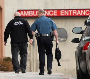 A police chaplain heads to the ambulance entrance at UCHealth Memorial Hospital Central following a shooting in Colorado Springs, Colo., Monday, Feb. 5, 2018. (Jerilee Bennett/The Gazette via AP)