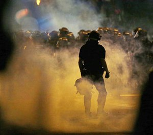 Police fire teargas as protestors converge on downtown following Tuesday's police shooting of Keith Lamont Scott in Charlotte, N.C., Wednesday, Sept. 21, 2016. (AP Photo/Gerry Broome)