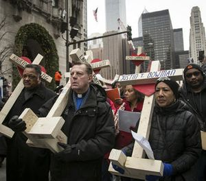 The Rev. Michael Pfleger, third from left, the Rev. Jesse Jackson, second from left, and state Sen. Jacqueline Collins, right, led hundreds in a march down Michigan Avenue, carrying crosses for all those killed by Chicago violence in 2016 and to call for an end to violence in 2017, Saturday, Dec. 31, 2016, in Chicago. (Ashlee Rezin/Chicago Sun-Times via AP)