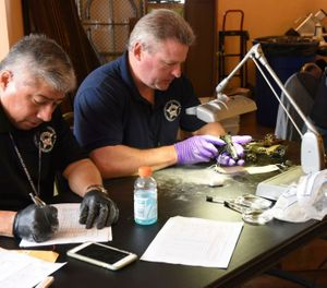 Forensic firearms examiners inspect weapons turned in by residents in a gun buy-back program (Photo/ Chicago Police Department via Associated Press)