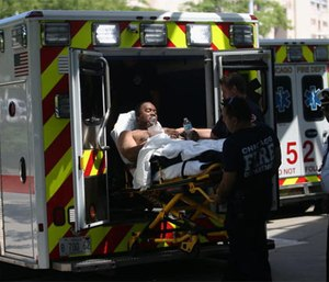 One of three injured firefighters is wheeled into Stroger Hospital on July 31, 2016, after a residential fire. (Brandon Chew/Chicago Tribune)