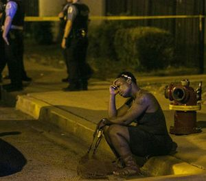 In this Aug. 7, 2016, file photo, a woman sits on the curb as police in the background investigate the scene where gunfire at a birthday party left a man dead and a woman injured. (Ashlee Rezin/Chicago Sun-Times via AP, File)