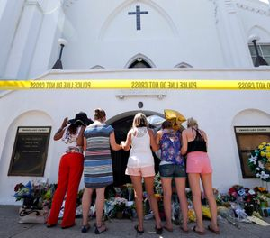 In this June 18, 2015, file photo, a group of women pray together at a makeshift memorial on the sidewalk in front of the Emanuel AME Church, in Charleston, S.C. (AP Photo/Stephen B. Morton, File)