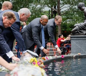 Mourners place flowers at the fountain edge before a vigil in Fountain Square where a shooting took place the previous day that claimed the lives of three civilians, Friday, Sept. 7, 2018, in Cincinnati. (AP Photo/John Minchillo)