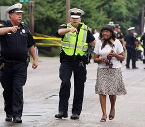 Cincinnati police lead a woman away from an area where an officer-involved shooting occurred Friday. (AP image)