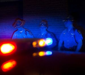 Police officers are illuminated by patrol car lights, Saturday, May 23, 2015, in Cleveland. (AP Photo/John Minchillo)