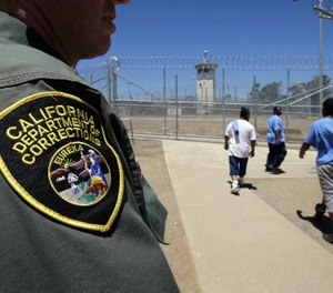 In this June 20, 2018 file photo , inmates pass a correctional officer as they leave an exercise yard at the California Medical Facility in Vacaville, Calif. (AP Photo/Rich Pedroncelli, file)