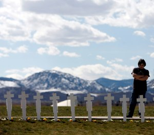 Garrett Bentley looks at a display of crosses for the 13 victims of the massacre at Columbine High School to mark the 10th anniversary of the killings near the Columbine Memorial in the southwest Denver suburb of Littleton, Colo., on Monday, April 20, 2009. (AP Photo/Jack Dempsey)
