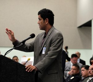 Los Angeles police Chief Charlie Beck, right, closes his eyes as Francisco Ortega, a human relations analyst, tries to calm the crowd during a community meeting in Los Angeles, Wednesday, Sept. 8, 2010. (AP Photo/Jae C. Hong)