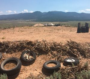A makeshift shooting range stands adjacent to a disheveled living compound in Amalia, N.M., on Tuesday, Aug. 7, 2018.  (AP Photo/Morgan Lee)