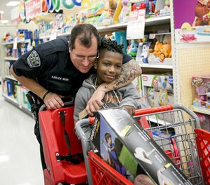 In this Dec. 15, 2016 file photo, Austin Police officer David Easley puts a tattooed arm around Jarvis Moblin, 8, in a hug during the 14th annual Shop With A Cop shopping spree at a Target in Austin, Texas. (Jay Janner/Austin American-Statesman via AP, File)