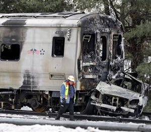 This Feb. 4, 2015 file photo shows a man looking over the wreckage of a a Metro-North Railroad train and an SUV in Valhalla, N.Y. (AP Image)