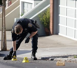 A San Francisco Police officer places a marker on the street after shootings in San Francisco, Wednesday, Nov. 1, 2017. (AP Photo/Jeff Chiu)