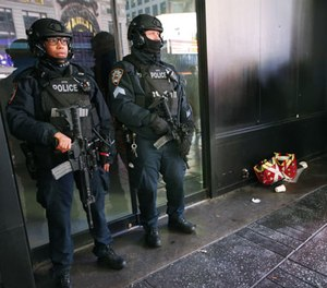 Heavily armed counterterrorism officers take shelter from the rain beneath an overhang in Times Square, Thursday, Dec. 29, 2016, in New York. (AP Photo/Kathy Willens)