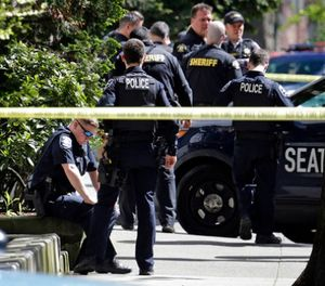 A Seattle police officer sits with his hands on his knees near the scene of a shooting involving several police officers in downtown Seattle, Thursday, April 20, 2017. (AP Photo/Elaine Thompson)