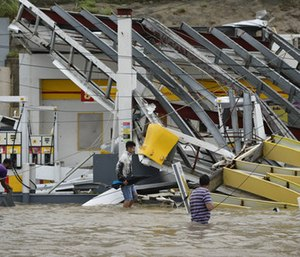 People walk next to a gas station flooded and damaged by the impact of Hurricane Maria, which hit the eastern region of the island, in Humacao, Puerto Rico. (Photo/AP)