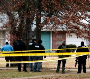 Police officers work the scene where two St. Louis County officers were shot and a man barricaded himself inside a home on Thursday, Dec. 14, 2017, in the St. Louis County town of Bellefontaine Neighbors, Mo. (Robert Cohen/St. Louis Post-Dispatch via AP)