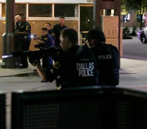 In this July 7, 2016, file photo, Dallas police move to detain a driver after several police officers were shot in downtown Dallas. (AP Photo/LM Otero, File)