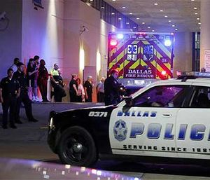 A Dallas ambulance and police car are stationed outside the ER. (AP Image)
