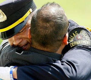 A Dallas police officer gets a hug after an honor guard ceremony for Dallas police officer Patrick Zamarripa at Dallas-Fort Worth National Cemetery in Dallas, Saturday, July 16, 2016. (AP Photo/LM Otero)