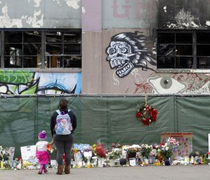 In this Dec. 13, 2016, file photo, flowers, pictures, signs and candles, are placed at the scene of a warehouse fire in Oakland, Calif. (AP Photo/Marcio Jose Sanchez, File)