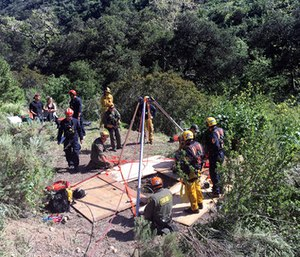Rescue workers help rescue a dog out of a well in the mountains outside of Malibu, Calif. (Los Angeles County Fire Department via AP)
