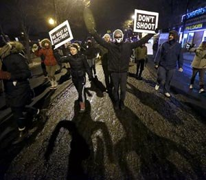 Protesters march during a rally near the Chicago Police headquarters after the announcement of the grand jury decision not to indict police officer Darren Wilson in the fatal shooting of Michael Brown, an unarmed black 18-year old, Monday, Nov. 24, 2014, in Chicago. (AP Image)