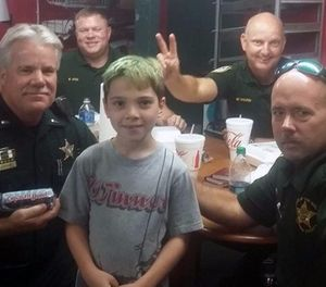 This picture captures Tyler Carach posing with the very first LEOs he gave donuts to. (Photo/Sheena Carach)