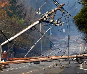 People walk past a fallen transformer and downed power lines on Parker Hill Road in Santa Rosa, Calif. (Nhat V. Meyer/San Jose Mercury News via AP)