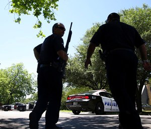Dallas Police walk a neighborhood a block away from a shooting in Dallas. (AP Photo/LM Otero)