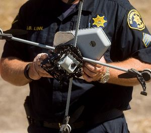 Sgt. Jim Linn retrieves the Alameda County Sheriff's Office drone while demonstrating a search and rescue operation on Friday, Aug. 14, 2015, in Dublin, Calif. (AP Photo/Noah Berger)