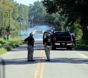 Responders congregate near where two people drowned the evening before when they were trapped in a Horry County Sheriff's transport van while crossing an overtopped bridge over the Little Pee Dee River on Highway 76, during rising floodwaters in the aftermath of Hurricane Florence in Marion County, S.C. Charges are expected to be filed Friday, Jan. 4, 2019, against two South Carolina law enforcement officers who were transporting two mental patients who drowned while locked in the back of a van during the hurricane. (AP Photo/Gerald Herbert, File)