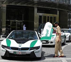 Dubai police Lt. Saif Sultan Rashed al-Shamsi  pushes down one of the twin scissor doors of the $140,000 BMW i8. (AP Image)