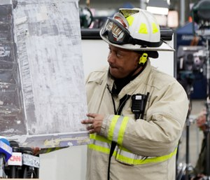 Oakland Fire Battalion Chief Darin White shows an aerial view of a warehouse fire. (AP Photo/Marcio Jose Sanchez)