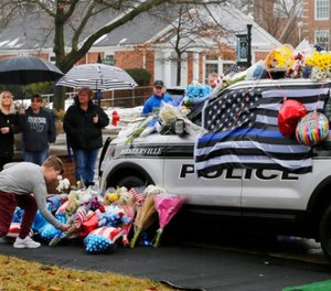Mourners gather and leave flowers on a police cruiser parked in front of City Hall in Westerville, Ohio, on Sunday, Feb. 11, 2018. (Sam Greene/The Cincinnati Enquirer via AP)