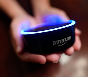 In this Thursday, Aug. 16, 2018, photo a child holds his Amazon Echo Dot in Kennesaw, Ga. (AP Photo/Mike Stewart)
