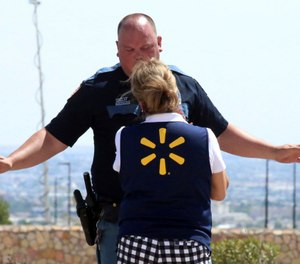 An El Paso police officer talks to a store employee following a shooting at a shopping mall in El Paso, Texas, on Saturday, Aug. 3, 2019. (AP Photo/Rudy Gutierrez)