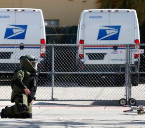 A member of the Miami-Dade County Police Bomb Squad looks for pieces of a suspicious package that was rendered safe after the bomb squad detonated the package that was found by a U.S. Postal employee who noticed what appeared to be wires coming out of an envelope at a post office, Monday, Nov. 5, 2018, in Miami Beach, Fla. (AP Photo/Wilfredo Lee)