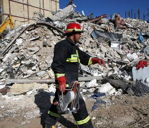 A rescue worker walks past the rubble of a collapsed building at an earthquake site in Sarpol-e-Zahab. (AP Photo/Vahid Salemi)