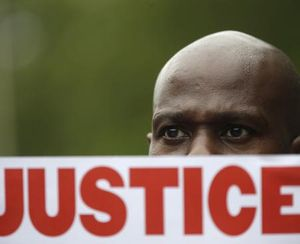 In this July 18, 2015 file photo, a demonstrator holds a sign calling for justice during a rally in New York were several hundred people rallied outside the federal courthouse in Brooklyn to demand action in the fatal chokehold death of Eric Garner by a white police officer. (AP File Photo/Mary Altaffer)