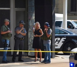 Officials consult near the crime scene at the Huntington Bank, next to the Courthouse in Steubenville, Ohio, Monday Aug. 21, 2017, after Jefferson County Judge Joseph Bruzzese Jr. was ambushed and shot while walking to work early Monday morning. (Darrell Sapp/Pittsburgh Post-Gazette via AP)
