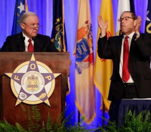 Attorney General Jeff Sessions, left, is applauded by Fraternal Order of Police National President Chuck Canterbury as Sessions addresses the group's convention Monday, Aug. 28, 2017, in Nashville, Tenn. (AP Photo/Mark Humphrey)