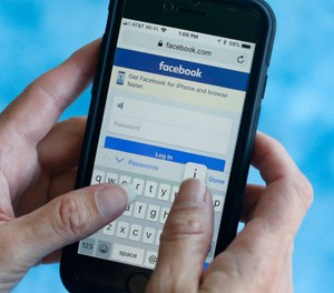 In this file photo dated Tuesday, Aug. 21, 2018, a Facebook start page is shown on a smartphone in Surfside, Fla. USA. (AP Photo/Wilfredo Lee, FILE)