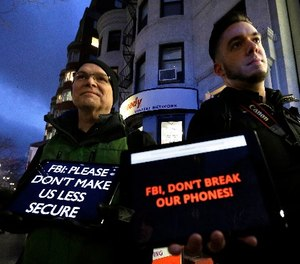 In this Tuesday, Feb. 23, 2016, file photo, demonstrators Peter Brockmann, of Northborough, Mass., left, and Chris Gladney, of Boston, right, display iPads with messages on their screens outside an Apple store in Boston. (AP Photo/Steven Senne, File)