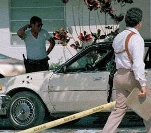 Law enforcement officials survey the scene of a shootout in which two FBI agents were killed and multiple other agents wounded, April 12, 1986. (AP Photo/Bill Cooke)