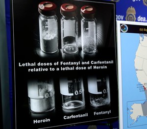 Posters comparing lethal amounts of heroin, fentanyl, and carfentanil, are on display during a news conference about the dangers of fentanyl, at DEA Headquarters in Arlington Va., Tuesday, June 6, 2017. (AP Photo/Jacquelyn Martin)