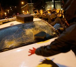 In this Nov. 25, 2014 file photo, protesters vandalize a police vehicle outside of Ferguson city hall in Ferguson, Mo. (AP Photo/David Goldman, File)